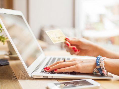 woman on computer holding credit card