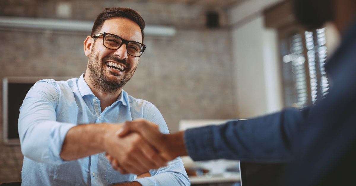 """alt=""""young business man shaking hands with out of frame person"""""""